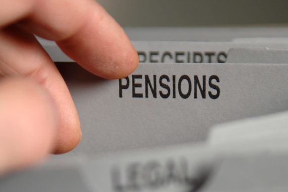 A hand flicks through files to find one marked 'pensions'