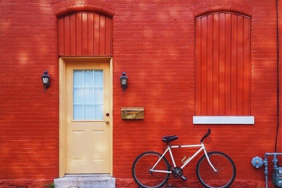 A red building with a cream door and a white bicycle in front of it