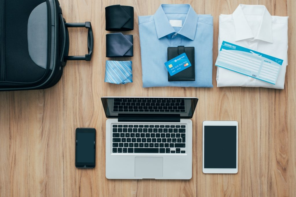 Business travel packing with shirts, computer, tablet, phone, ties, wallet, credit card, boarding pass and a suitcase