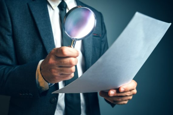 A businessman holds a magnifying glass to a document