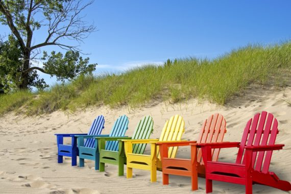Differently-coloured deckchairs on a beach