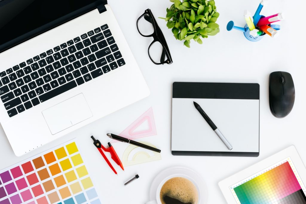 A designer's workspace with computer, tablet and colour charts