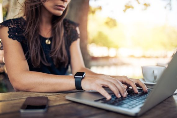 A woman with a smartwatch types on a laptop