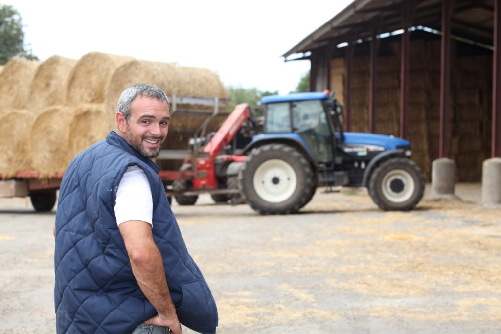 A smiling farmer in front of a tractor