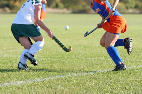 Two young women playing hockey