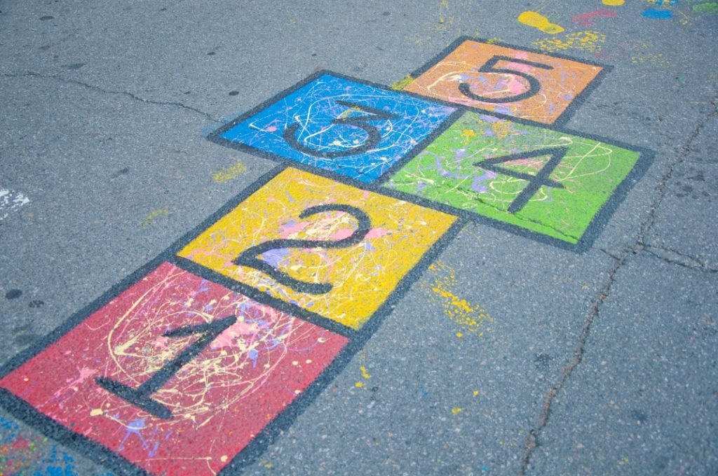 A colourful hopscotch grid chalked on a playground