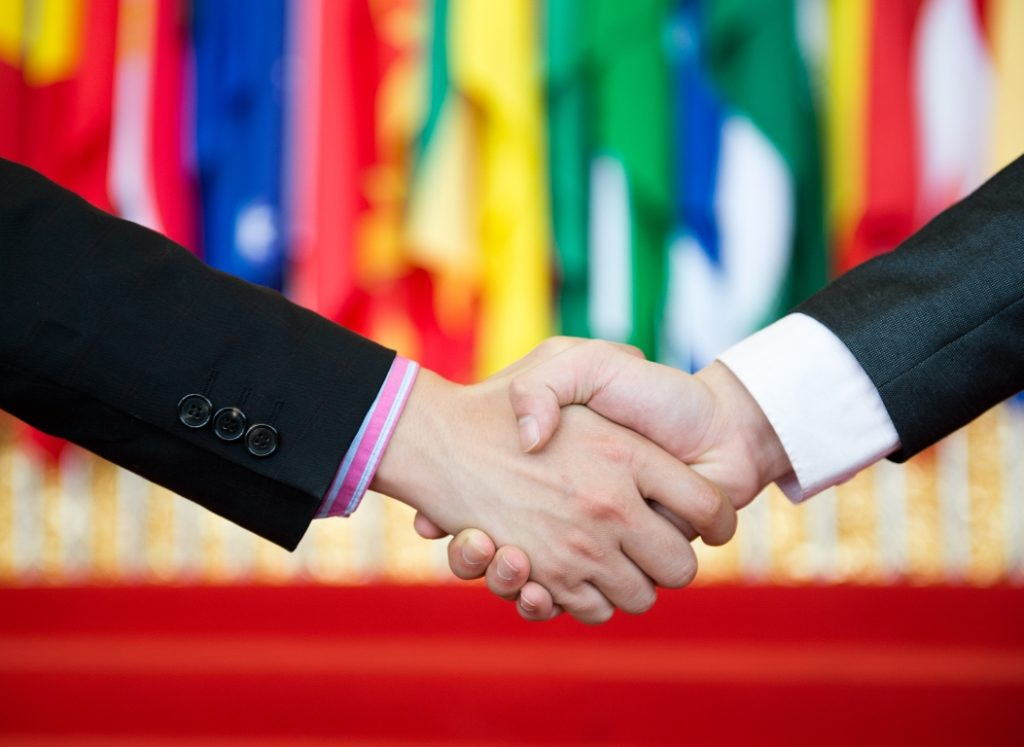 A handshake in front of a wall of flags