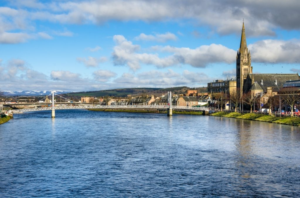 A bridge over a river in Inverness with a church on one bank