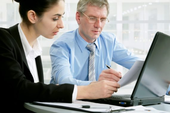 Two businesspeople working at a laptop