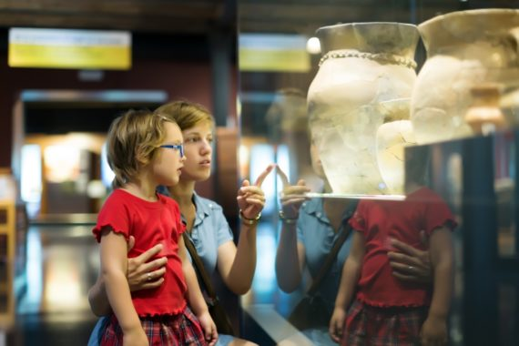 A woman shows a child a museum exhibit