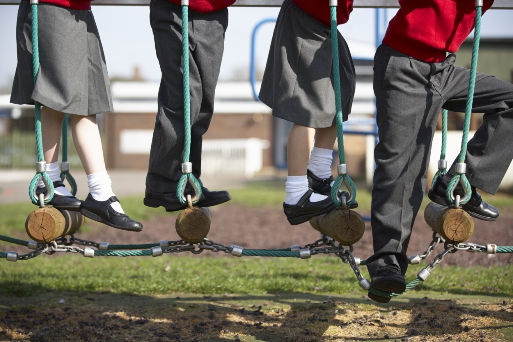 Four schoolchildren walking across an adventure playground