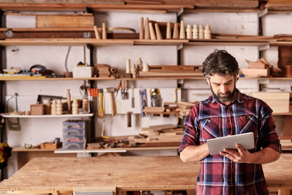 Man using tablet computer in a woodwork workshop