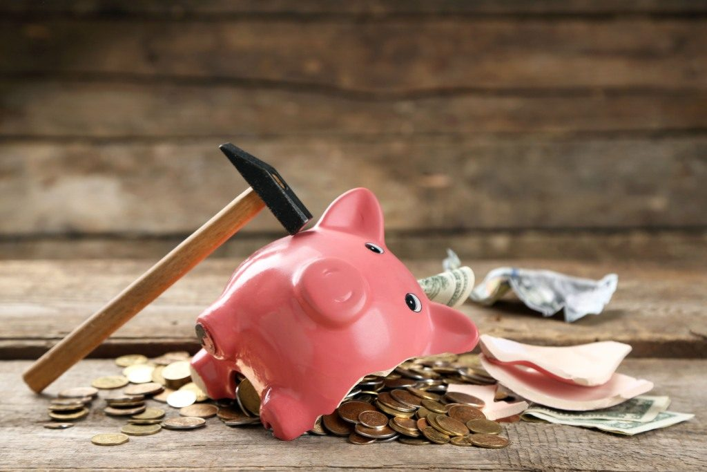 A piggy bank lies, smashed open by a hammer